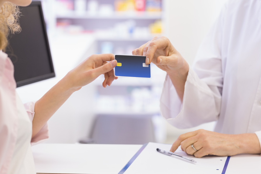 Pharmacist giving credit card to costumer at pharmacy